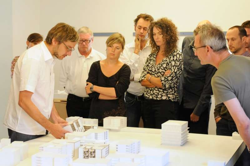 Community dialogue was integral to the development of Mehr Als Wohnen. Here, future residents and community members gather around a site model, which shows Christian Kerez' Leutschenbach School in one corner.